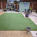 Artificial grass lawn surrounded by gravel and paving