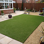 Artificial grass lawn surrounded by paving and gravel