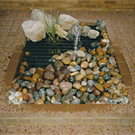 Small rectangular pond fountain with safety grill